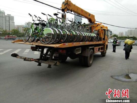 图为兰州交警部门采用拖车将随意停放的共享单车统一收集拖离。 史静静 摄