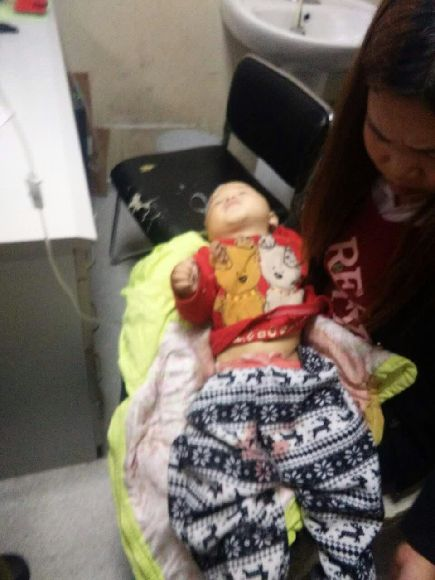 男童的姑姑张女士将男童抱在怀里,送往重庆儿童医院的路上。