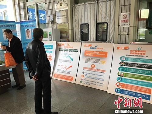 资料图:北京普仁医院外,有人在细读医改宣传板。汤琪 摄