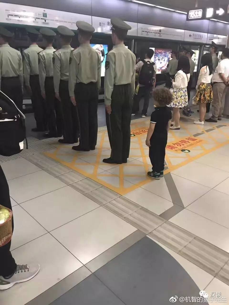 """图为网上热传""""榜样的力量""""照片,在奥林匹克公园站小男孩学习武警战士列队立正等车"""
