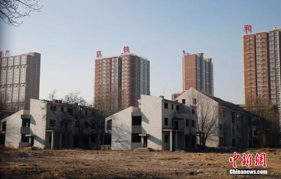 资料图:2013年12月13日,北京西二环京九铁路旁,20栋杂草丛中的烂尾别墅仍保持着23年前的模样。中新社发 张浩 摄