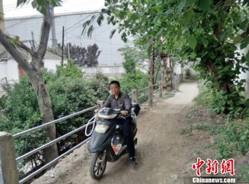 小区东门外住民骑车只能走这条坑洼小道。 朱志庚 摄