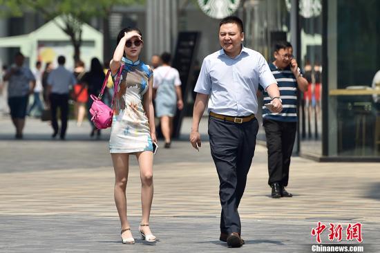 """5月17日,北京开启了高温干热的""""炙烤""""模式,图为北京三里屯街头市民穿夏装出行。 中新网记者 金硕 摄"""