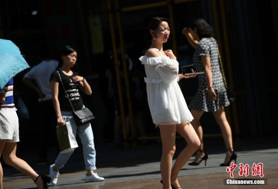 5月17日,观音桥步行街上美女着凉装出行。中新社记者 陈超 摄