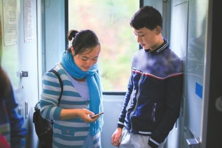 吉木呷呷在火车上用手机自学外语,旁边是她弟弟。