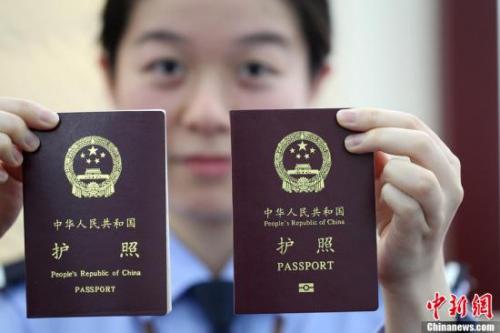 工作人员展示护照(资料图)。中新社发 许丛军 摄 图片来源:CNSPHOTO