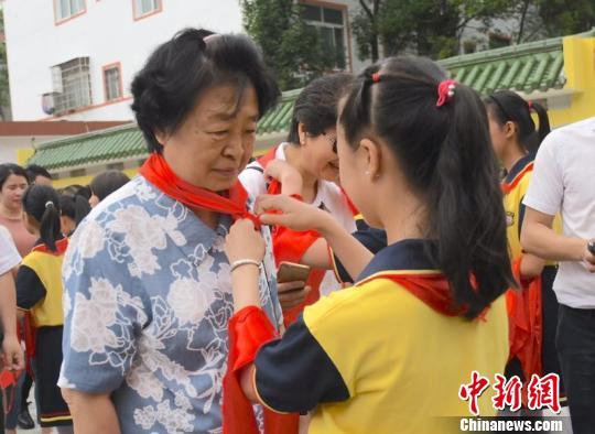 """图为""""临川八一希望小学""""少先队员给贺晓明戴红领巾。 钟欣 摄"""
