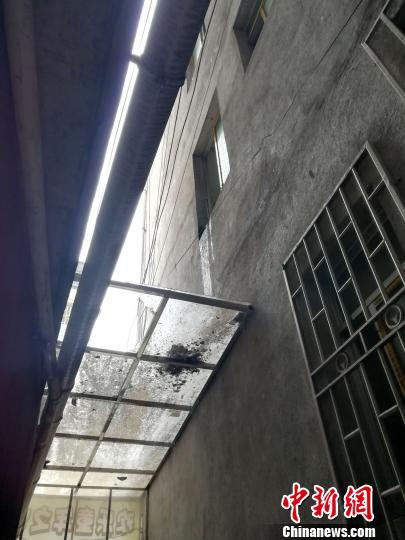 图为事发现场两栋民房间的挡雨棚玻璃被砸穿。 伍峰 摄