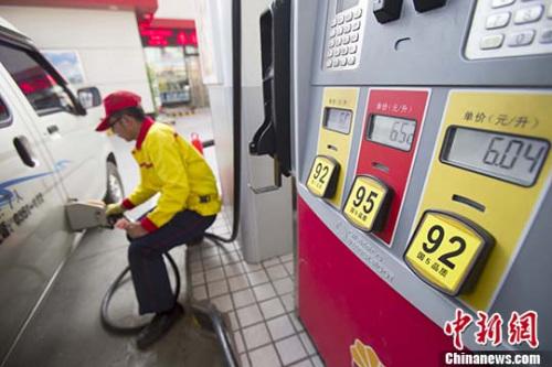 资料图:山西太原,加油站事情职员给车辆加油。 中新社记者 张云 摄