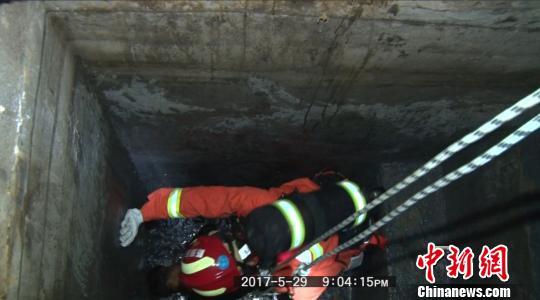 图为消防官兵下到沼气池内救人。 赵晨星 摄