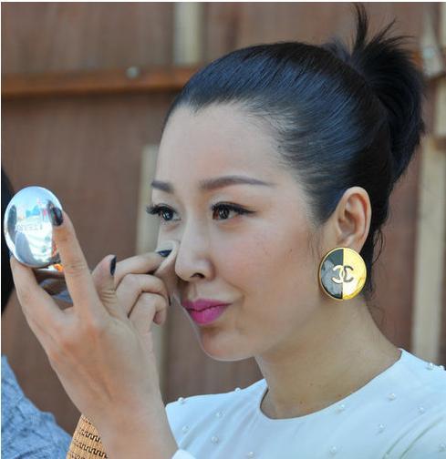 某次演出后台,孙悦亲自动手补妆,对镜露笑容怡然自得。不过,其耳朵上那副名牌耳环着实是亮点。