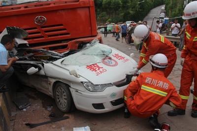 事故现场,教练车被大卡车压住 教练车司机被卡车内
