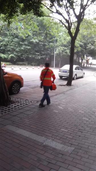 爆料人提供的环卫工人用鼓风机(图中圆圈处)扫街