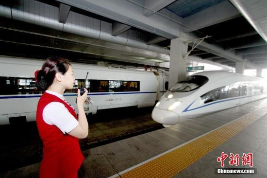 资料图:天津站高铁工作人员迎接入站的京津城际列车。中新社记者 张道正 摄