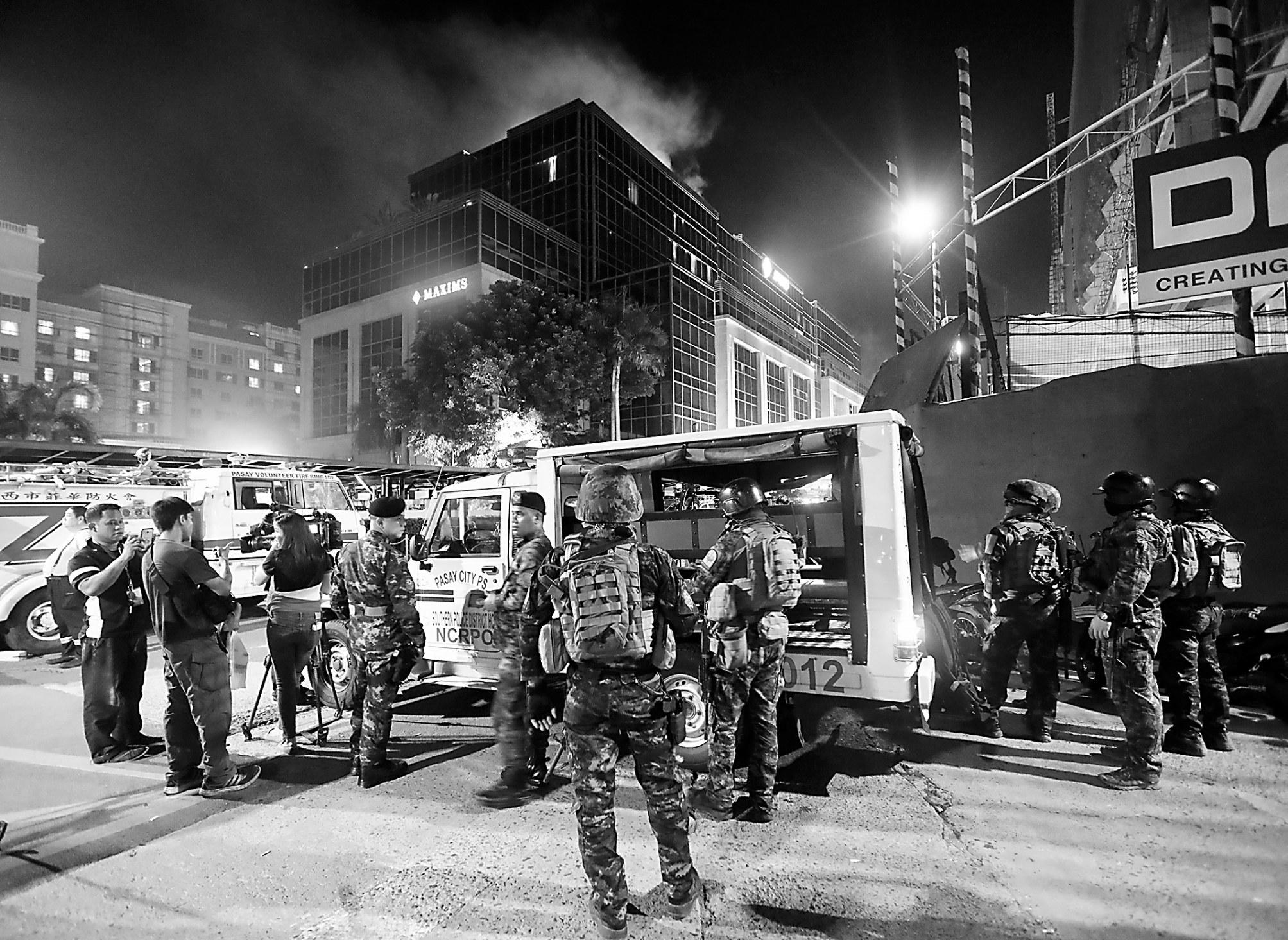 突击爆发后,菲律宾平安职员在旅店旁保持次序。