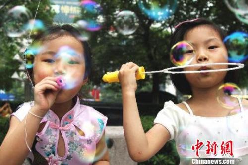 资料图:两名小女孩在南昌八一广场上吹泡泡。刘占昆 摄