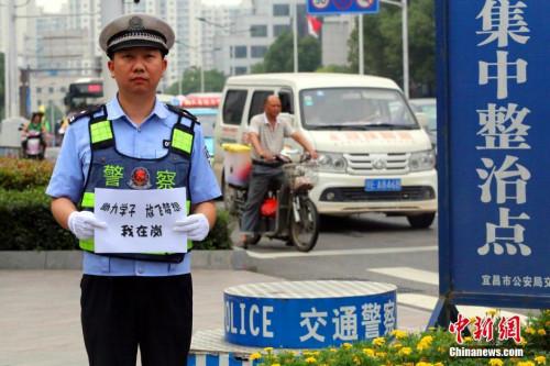 材料图:2016年6月6日,湖北省宜昌市公安局交警支队在城区7个考点部署专人批示交通,执勤平易近警也在考点前拍下自照相片,祝贺考生实现幻想。宜交宣 供图