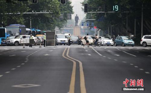 材料图;高考英语听力测验,南京交警将局部紧挨着科场的途径履行短时光关闭,免得乐音影响考生的测验。中新社发 泱波 摄