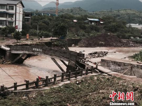 图为洪水将一座桥梁冲毁。 钟欣 摄