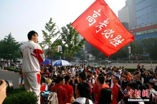 """2017年6月7日,北京人大附中考点外,学生挥舞""""高考必胜""""红旗为考生加油。中新社记者 韩海丹 摄"""