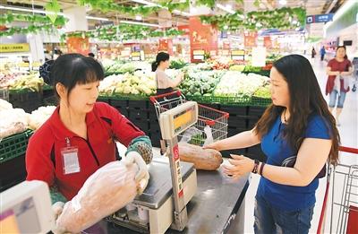 图为重庆市渝北区一超市工作人员(左)给消费者选购的南瓜称重。