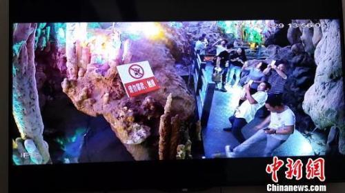 图为一游客在景区游玩时用力踢石钟乳。景区监控视频截图。