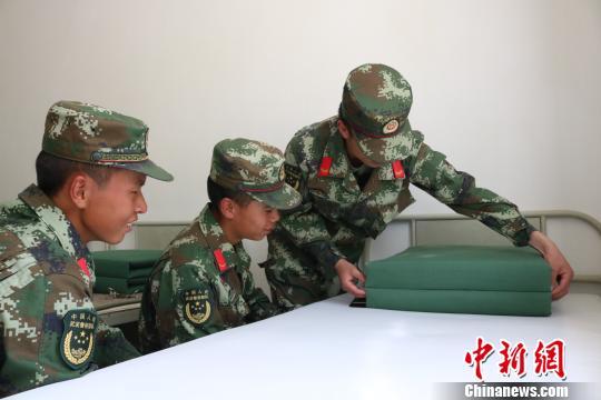 """图为武警西藏总队后勤仓库青年官兵在""""三帮一带""""活动中互帮技能提高。 余文彬 摄"""