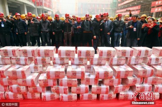 资料图:西安一工地发放1200万工资奖金,工人用旅行包装。马昭 摄 图片来源:视觉中国