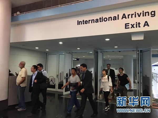 当地时间6月17日,章莹颖的父亲章荣高(左四)在芝加哥总领馆副总领事余鹏(左五)陪同下走出机场。新华网发