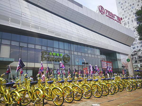酷骑新推出的金色共享单车被摆放在通州万达广场前的空地上展示。