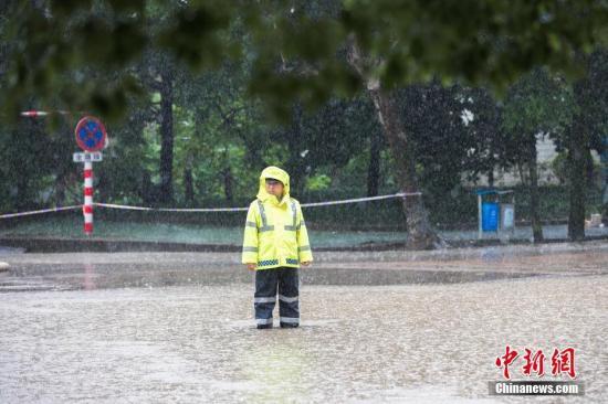 材料图:6月13日,浙江省金华市浦江县年夜雨滂湃,交警冒雨执勤,阻挡车辆进入漫水路段。 中新社发 张浩钺 摄