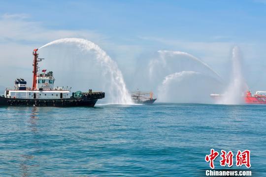 """图为演习中,救援船只喷出数条水柱,为""""失火""""渔船灭火。 骆云飞 摄"""
