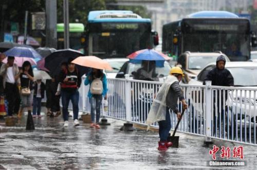 资料图:行人在雨中出行。 黄芷昕 摄