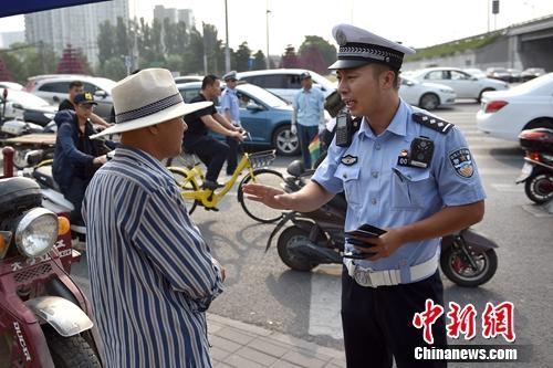 6月21日上午,北京交警敖翔处理交通违法行为。中新网记者 金硕 摄