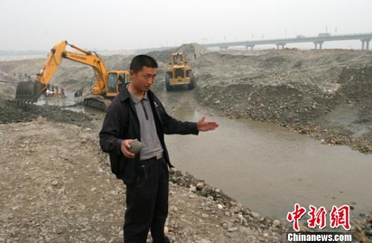 2005年彭山岷江施工过程当中发明几锭银锭,工人徒弟脚拿银锭先容情形。(材料图) 刘忠俊 摄