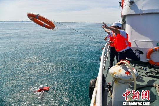 """演习中搜救人员发现""""落水者"""",抛出救生圈救援。 骆云飞 摄"""