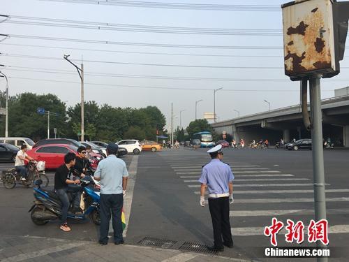 6月21日上午,北京仰山桥下十字路口,执勤人员要求非机动车停在停止线后。汤琪 摄