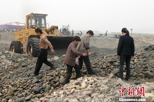 2005年彭山岷江一河滩工地挖出银锭后,当地一些村民在河滩上寻宝。(资料图) 刘忠俊 摄