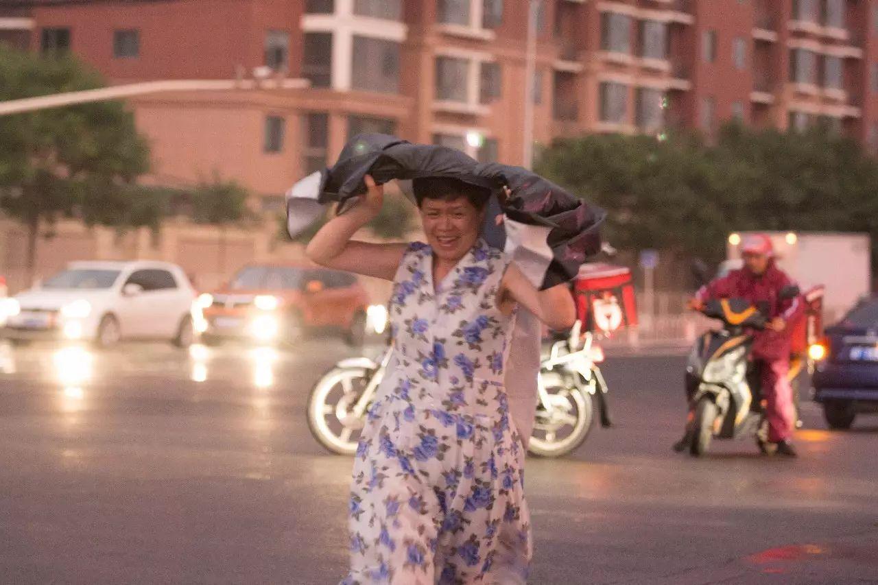 △6月21日,北京,降雨刚开端,路上的行人敏捷举动。