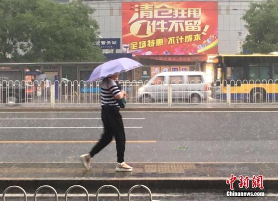 6月23日清晨,北京市民冒雨出行。 中新网记者 富宇 摄