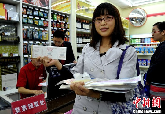 图为一位纳税人展示在超市刚领取的发票。中新社发 刘忠俊 摄