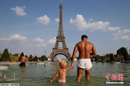 法国巴黎,人们在埃菲尔铁塔前的TROCADERO广场上玩水,以逃避高温。