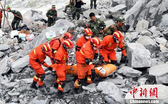 救援职员将罹难者遗体抬出垮塌现场。 安源 摄