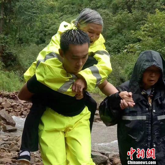 图为:遂昌一位民警将自己的衣服穿在老人身上,并背起老人向宁静地带转移。 徐民哲(通讯员) 摄