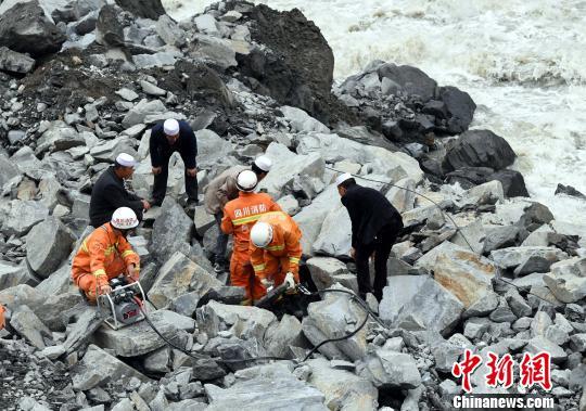 当地村民配合救援职员到场救援。 安源 摄