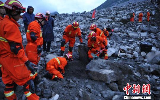 救援职员在挖掘罹难者遗体。 刘忠俊 摄