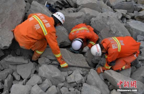 救火员正在现场寻觅掉联者。中新社记者 刘忠俊 摄