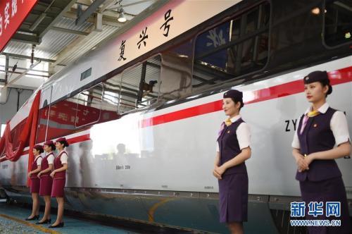 """6月25日,乘务人员站在""""复兴号""""中国标准动车组CR400AF型列车旁。新华社记者 鞠焕宗 摄 图片来源:新华网"""