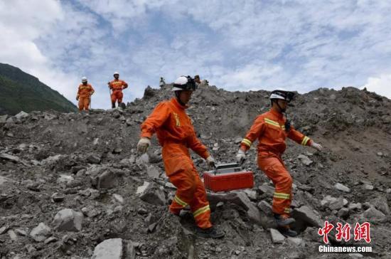 6月25日,消防官兵抬生命探测仪征采幸存者。 姜学华 摄