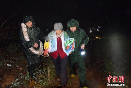 资料图:消防官兵冒雨紧急护送民众转移至安全地带。 吴从昊 摄